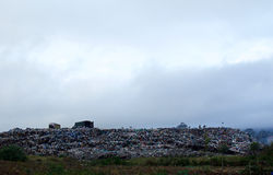 Rubbish mound. Being managed by people on a misty morning while more is supplied by the truckload Royalty Free Stock Photos