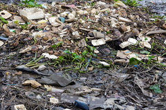 Rubbish pollution on a river bank Royalty Free Stock Images