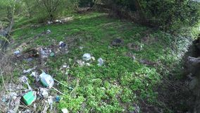 Rubbish on the river bank. Dynamic panorama of rubbish on the bank of a small river stock video footage