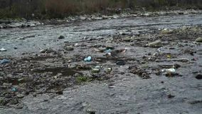 Rubbish on the river. Garbage in a mountain river. Environmental pollution. Pollution of nature. Ecological catastrophy