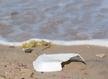 Rubbish on sandy beach. Closeup of polystyrene rubbish on sandy beach with water Stock Photo