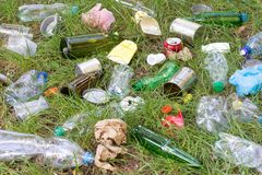 Rubbish such as plastic and glass bottles, tins, cans and pieces of paper on grass royalty free stock photography