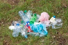Rubbish such as plastic and glass bottles, tins, cans and pieces of paper on grass stock images