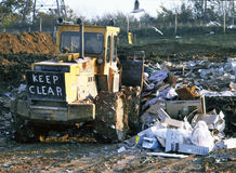 Rubbish tip at landfill site with bulldozer at work Royalty Free Stock Photography