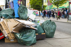 Rubbish and waste on the sidewalk of a busy street Royalty Free Stock Photography