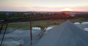 Rubble barrow under brown rusty support against rising sun. Picturesque rubble barrow under brown rusty support against setting sun aerial view. Concept stock video