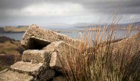 Rubble of a crumbling cottage with storm approaching. The concrete bricks of an old crofter's cottage lay in rubble on a hilltop with a storm threatening to Stock Photo