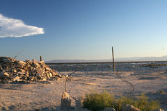 Rubble dumped at Salton Sea. A pile of rubble sits next to the Salton Sea with mountains in the background Royalty Free Stock Photos
