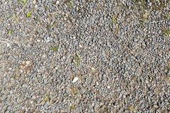 Rubble evenly distributed on the soil. Small stones on the path,. With grass grown on the sides, dry summer weather Royalty Free Stock Images