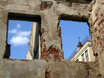 Rubble in oldtown. Tower of the church visible trough the hole of the window Royalty Free Stock Photos
