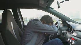 Rubbning och ilsket affärsmansammanträde för blandat lopp inom hans bil utomhus stock video