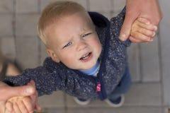 Rubbning tröttat litet barn som upp till ser fadern Top beskådar royaltyfria foton