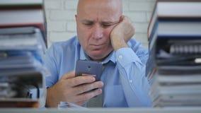Rubbningaffärsman Looking till mobiltelefonmeddelandet med en besviken inställning royaltyfri fotografi