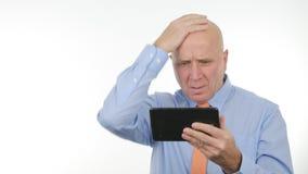 RubbningaffärsmanReading Amazed Bad nyheterna på minnestavlan och göra en gest som är nervöst arkivbilder