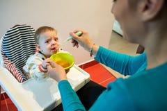 Rubbningen behandla som ett barn äta fast mat från en sked differentiering royaltyfri bild