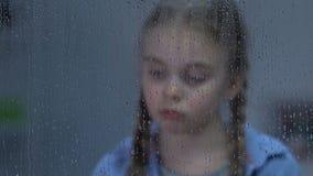 Rubbningflicka som ser i fönster på regn och att lida ensamhet, väntande föräldrar stock video
