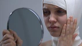 Rubbningkvinna i headwrapen som ser spegelreflexionen, mislyckad kirurgi stock video