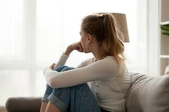 Rubbningkvinna som hemma sitter på soffan bara arkivbilder