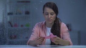 Rubbningkvinna som rymmer rosa sockor av det ofödda barnet på den regniga dagen, ofruktbarhetproblem arkivfilmer