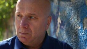 Rubbningperson nära en vägg från gatan som ser besviket bekymrat och den besvärar lager videofilmer