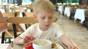 Rubbningpysen som äter havremjölet i restaurangen, önskar han inte att äta stock video