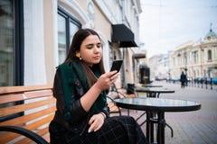 Rubbningung flickastudent som rymmer en smartphone och känner sig missbelåten Tunga utbildning och massor av jobb satte henne i arkivfoto