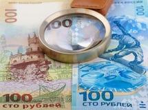 100 Rubel Banknote und Vergrößerungsglas Stockfotografie