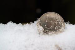 5 Rubel in der Schneewehe, der einfrierende Rubel während der Krise Stockfotos