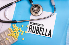 Rubella word written on medical blue folder with patient files. Pills and stethoscope on background royalty free stock image