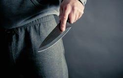 Räuber, der ein großes Messer stößt Lizenzfreie Stockfotos