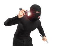 Räuber, der eine Taschenlampe und ein Stück des Rohres anhält Stockfoto