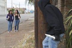 Räuber, der hinter Baum sich versteckt und auf zwei Mädchen wartet Stockfoto