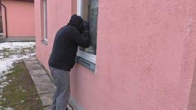 Räuber mit Brechstange aufpassend in Fenster stock footage