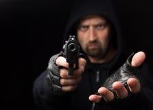 Räuber mit der Gewehr, die heraus Hand anhält Lizenzfreie Stockfotografie