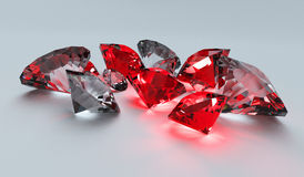 Rubies and Diamonds. A collection of rubies and diamonds scattering light on a plane white surface Royalty Free Stock Photography