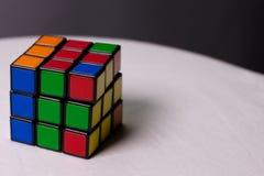 Rubik& x27 ; cube en s pour le fond sur une table blanche Image stock