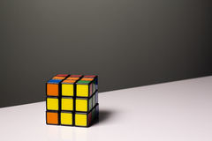 Rubik& x27; cubo di s per i precedenti su una tavola bianca Immagine Stock Libera da Diritti