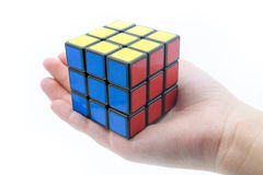 Rubik`s cube is holden by hand isolated on white background royalty free stock photography