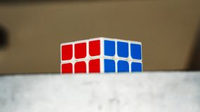 Rubik`s Cube on the table. NRubik`s cube lying on the table. Blur effect, focus on the cube. Two colors are visible, blue and red Royalty Free Stock Image