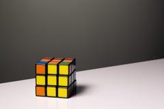 Rubik& x27; s-kub för bakgrunden på en vit tabell Royaltyfri Bild