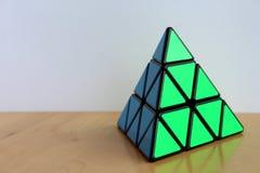 Rubik` s Pyraminx Kubus op een Lijst stock afbeelding