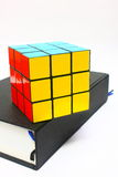 Rubiks Cube on Book. Solved rubiks cube on top of thick book isolated on white background Stock Photography