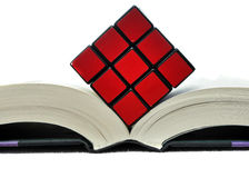 Rubiks Cube on Open Book. Puzzle cube on top of thick book isolated on white background Stock Image