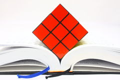 Rubiks Cube on Open Book. Puzzle cube on top of thick book isolated on white background Royalty Free Stock Image