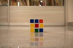 Rubiks kub som lägger på golvet royaltyfria bilder