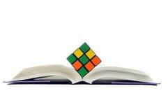 Rubiks Würfel auf geöffnetem Buch Stockfotografie