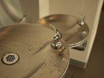 Rubinetti e lavandino di acqua nell'interno pubblico Immagine Stock