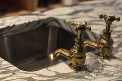 Rubinetti e marmo dell'oro fotografia stock libera da diritti