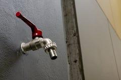 Rubinetto del rubinetto di acqua nel colore rosso sulla parete in bagno grigio scuro e riflette sul concetto dell'acqua di rispar fotografia stock libera da diritti