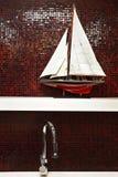 Rubinetto dell'acciaio inossidabile con il modello della barca a vela sullo scaffale con il picchiettio rosso immagine stock libera da diritti